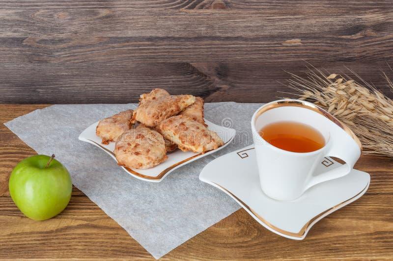 Taza de té, de Apple y de trigo en un fondo de madera imágenes de archivo libres de regalías