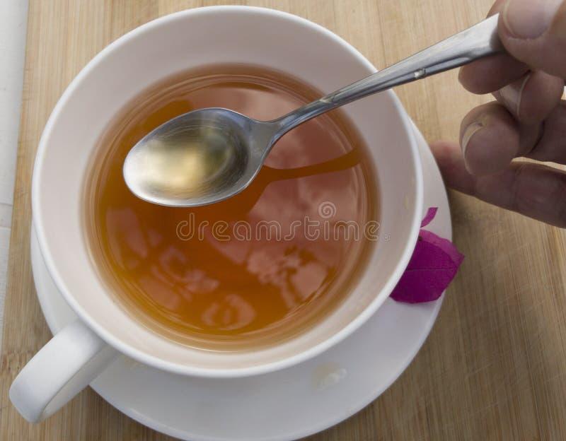 Taza de t? blanca con infusi?n de hierbas y una cuchara de plata foto de archivo libre de regalías