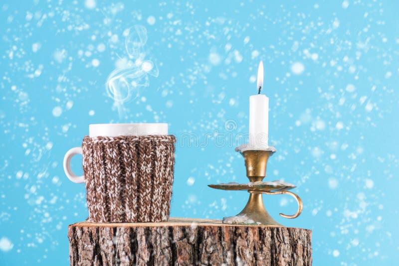 Taza de té caliente en bufanda de las lanas y de vela en el palillo de la vela que quema en el registro de madera fotografía de archivo
