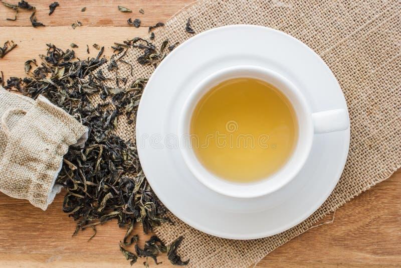 Taza de té caliente en harpillera con el bolso secado de la forma del desbordamiento de las hojas de té fotos de archivo