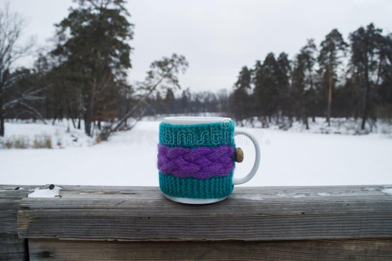 Taza de té caliente en una cubierta de punto imagen de archivo libre de regalías