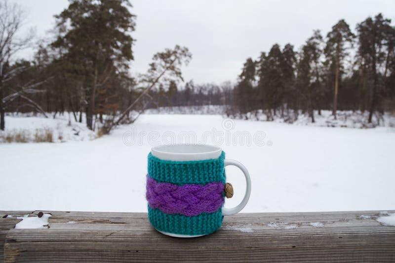 Taza de té caliente en una cubierta de punto imagenes de archivo