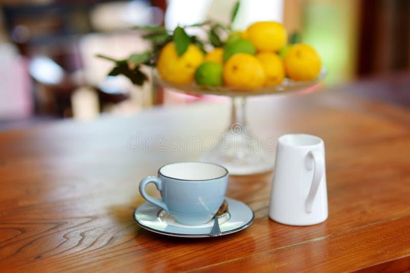 Taza de té de cerámica azul hermosa en una tabla de madera, con un plato de limones en el fondo fotos de archivo libres de regalías