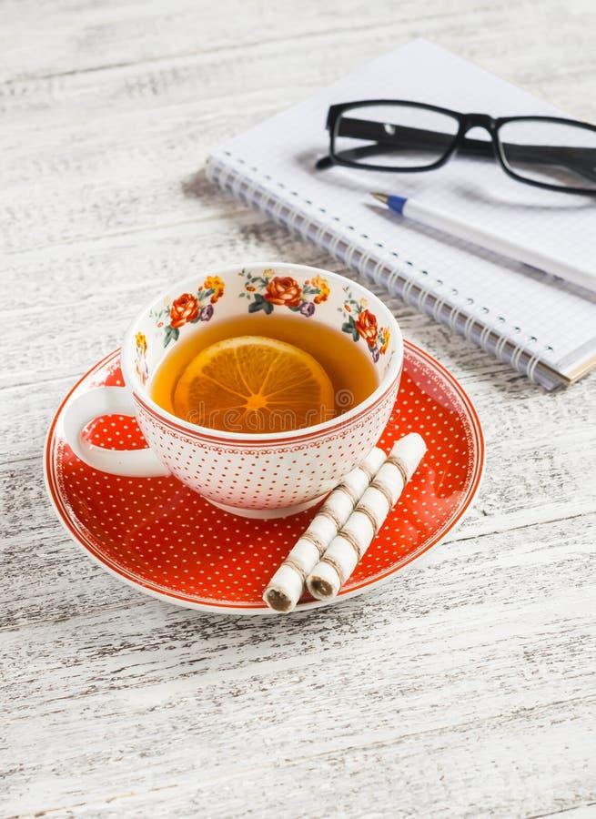 Taza de té con el limón, galletas y un cuaderno en blanco abierto fotografía de archivo libre de regalías