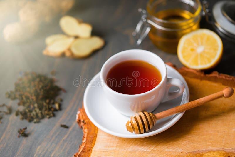 Taza de té con el limón, el jengibre, la miel y el palillo de la miel en la tabla rústica de madera fotos de archivo libres de regalías