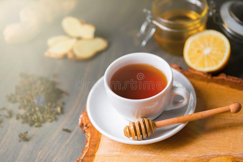 Taza de té con el limón, el jengibre, la miel y el palillo de la miel en la tabla rústica de madera fotografía de archivo
