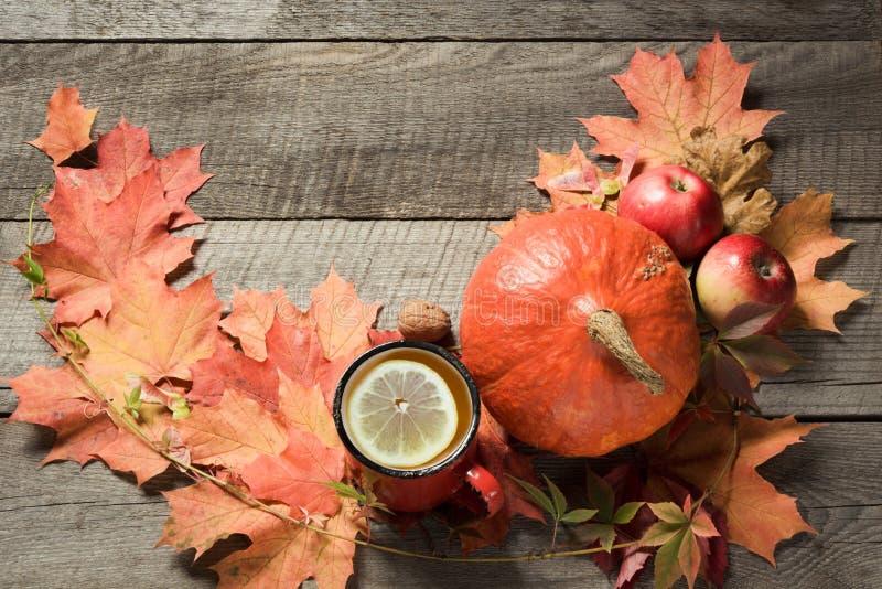Taza de té con la decoración de las hojas y de las calabazas de otoño en el tablero de madera Todavía de la caída vida fotos de archivo