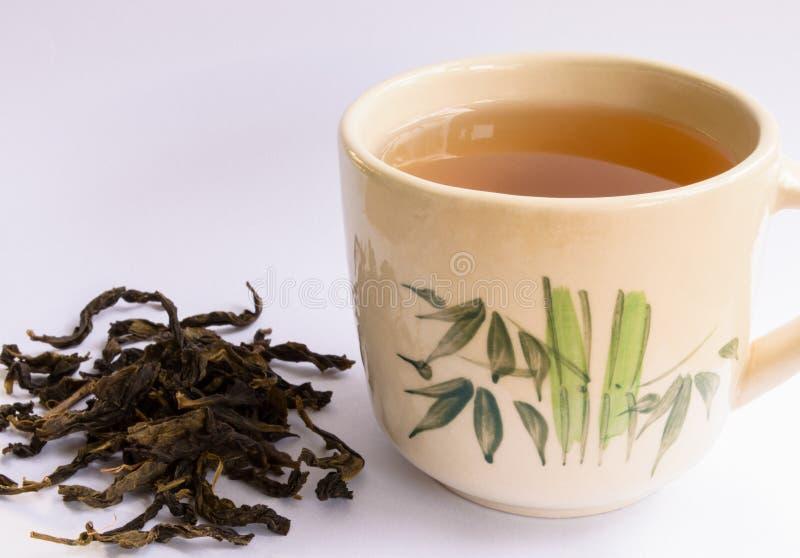 Taza de té con la hoja de té imagenes de archivo