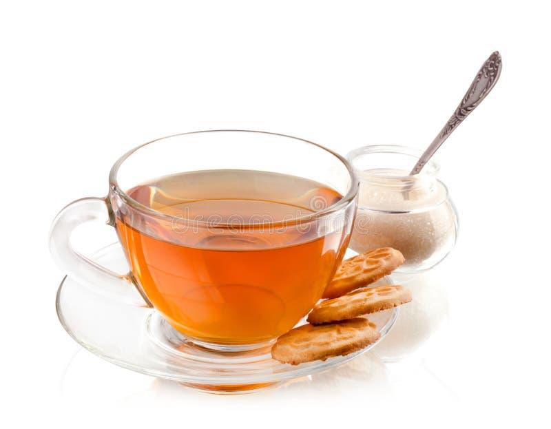 Taza de té con las galletas y el azúcar en un blanco imagen de archivo