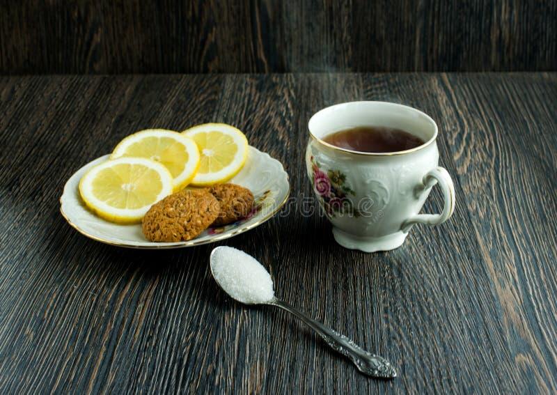 Taza de té con las galletas y el limón en el top, de té caliente con el limón y de azúcar imagen de archivo libre de regalías