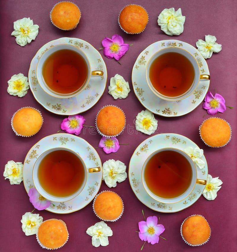 Taza de té con las tortas y las rosas fotografía de archivo libre de regalías