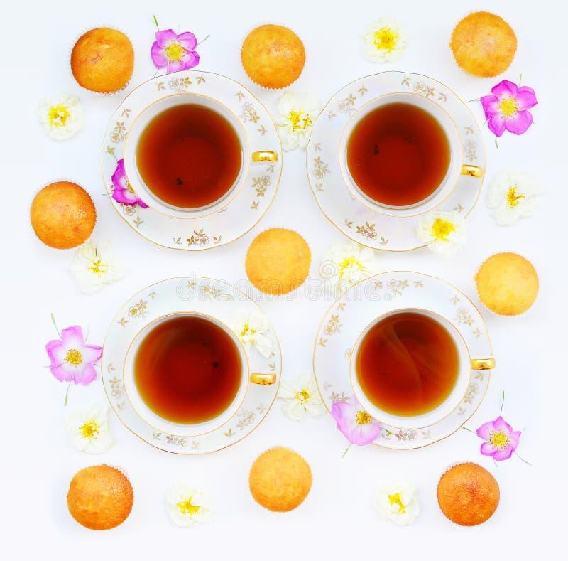 Taza de té con las tortas y las rosas foto de archivo