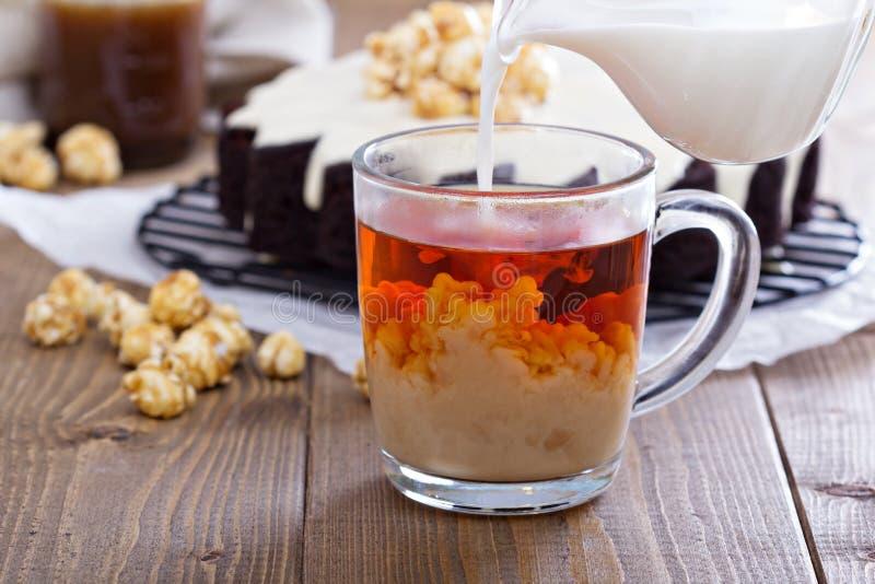 Taza de té con leche negro imagen de archivo