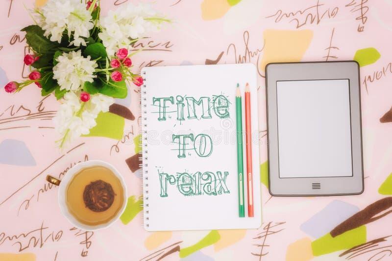 Taza de té, cuaderno y ebook imagenes de archivo