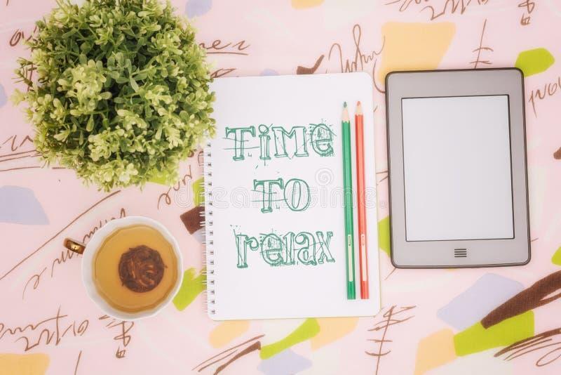 Taza de té, cuaderno y ebook foto de archivo