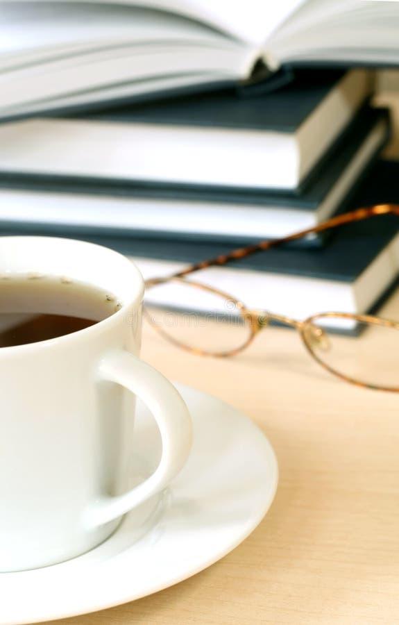 Taza de té, de libros y de lentes fotografía de archivo