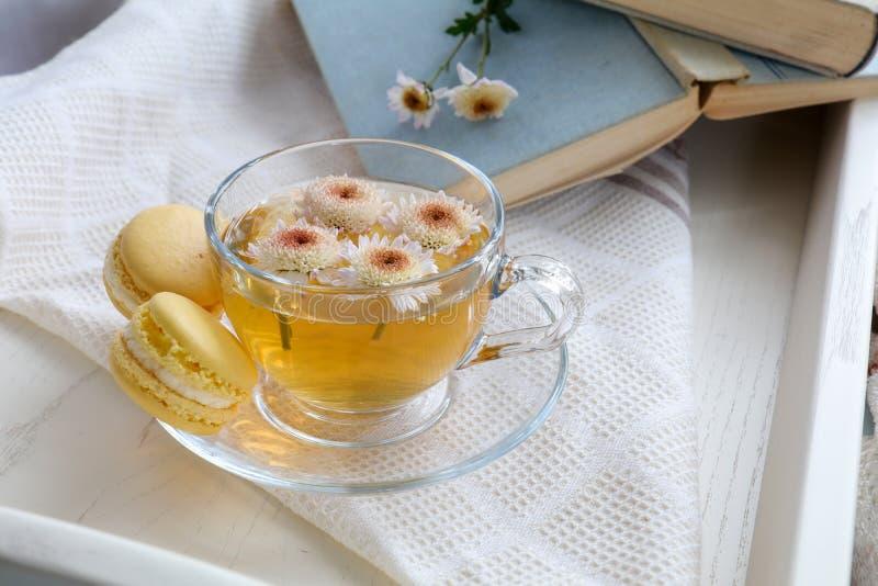 Taza de té, de macarrones, de flores del crisantemo y de libros imagen de archivo libre de regalías