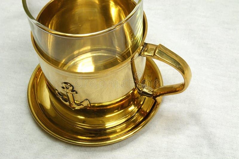 Taza de té de oro foto de archivo libre de regalías