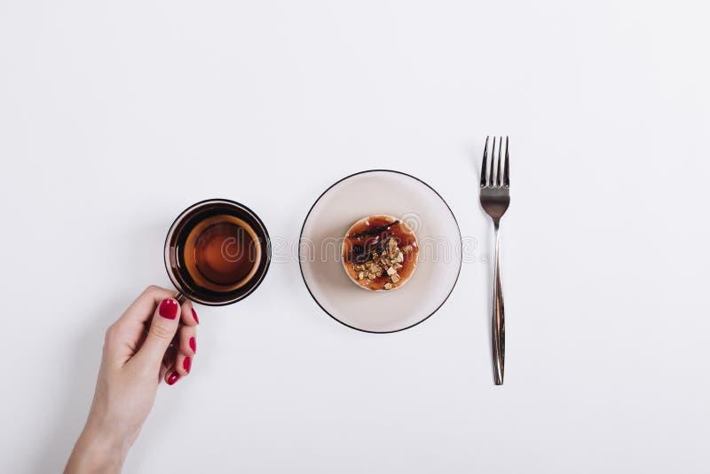 Taza de té, de torta y de bifurcación en una tabla blanca, una mano femenina con r foto de archivo libre de regalías
