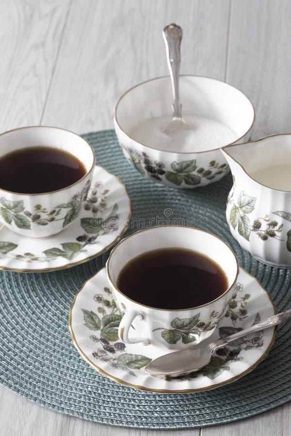 Taza de té en el platillo con el jarro de leche de la cucharilla y el cuenco de azúcar en un placemat verde fotografía de archivo libre de regalías