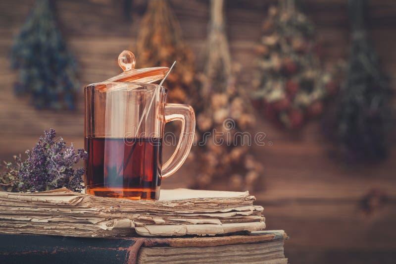 Taza de té en la pila de libros viejos Manojos de la ejecución de hierbas medicinales en fondo imagen de archivo