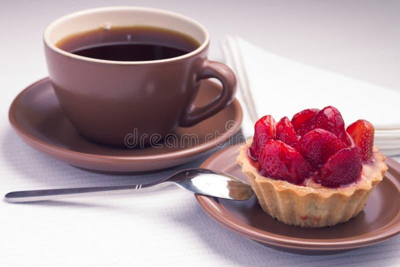 Taza de té en la servilleta blanca con el postre de la fresa fotografía de archivo libre de regalías