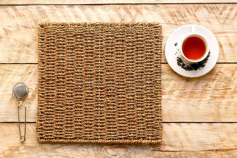 Taza de té en una estera de mimbre con el tamiz fotografía de archivo