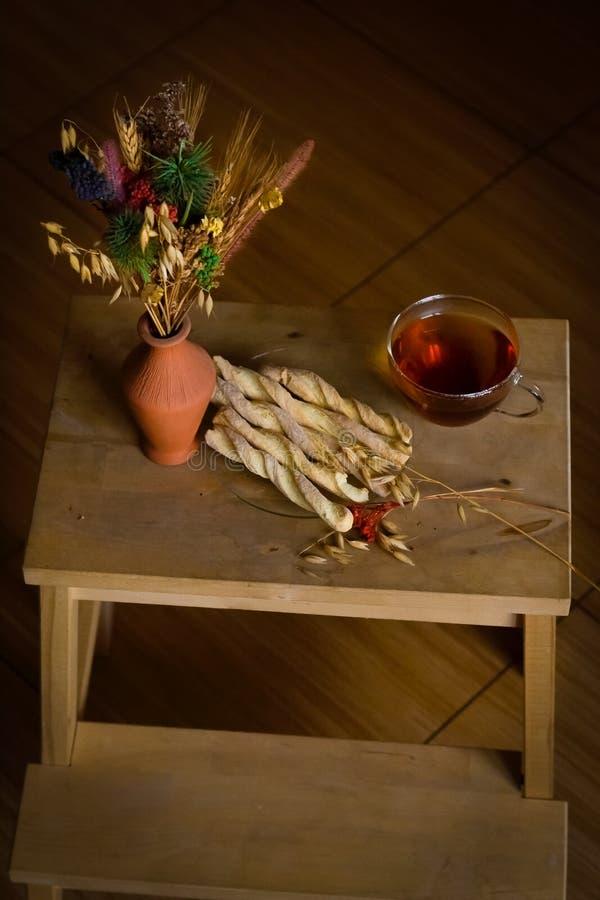 Taza de té, de galletas y de flores secadas foto de archivo libre de regalías
