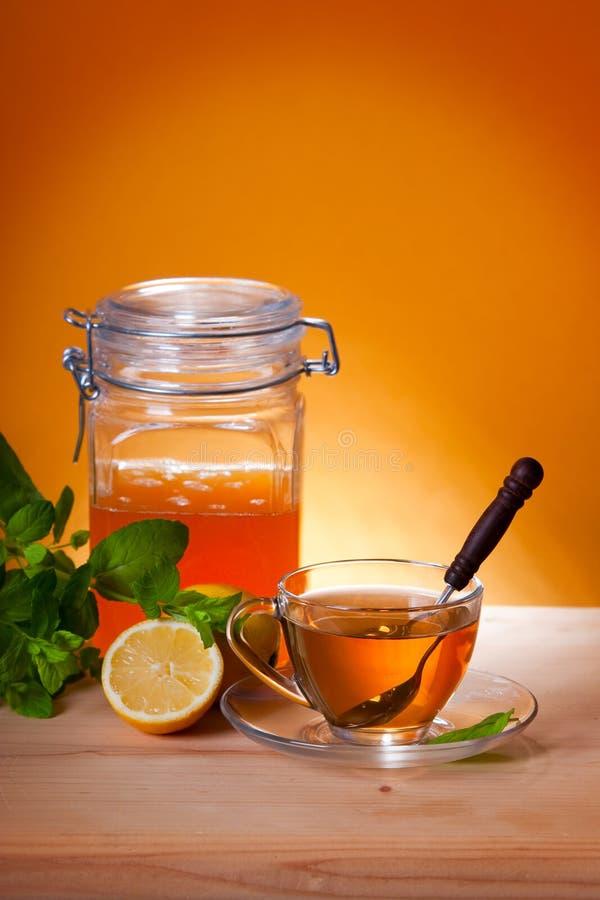 Taza de té herbario y de miel fotos de archivo