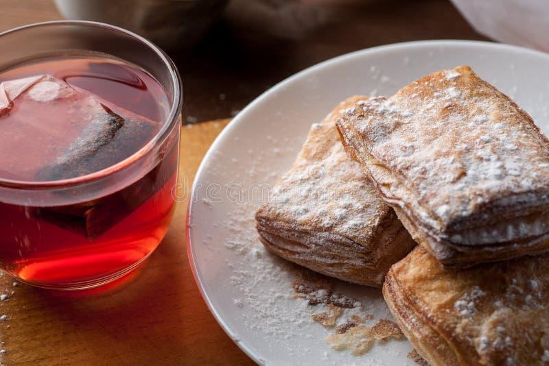 Taza de té de la fruta con las galletas de la pasta de hojaldre en una tabla de madera, foco selectivo fotografía de archivo libre de regalías