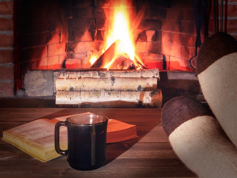 Taza de té, libro, los pies de las mujeres en calcetines calientes en una tabla de madera enfrente de una chimenea ardiente fotografía de archivo libre de regalías