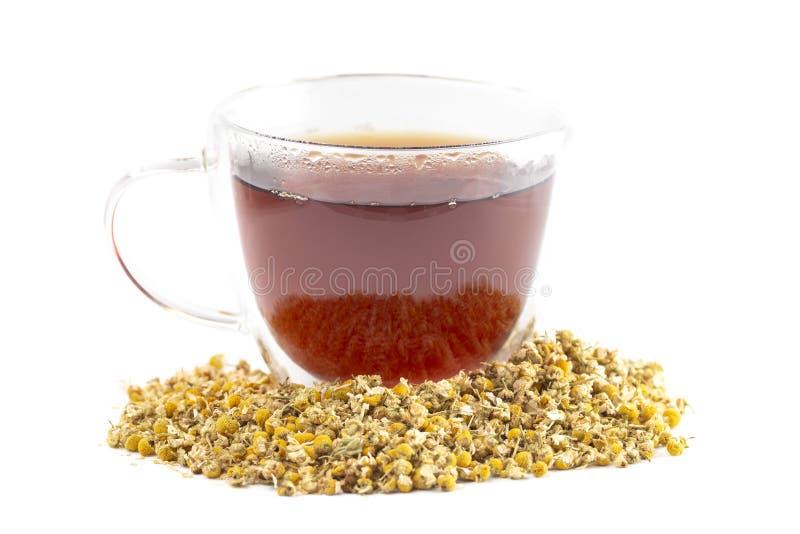 Taza de té de manzanilla caliente con las flores secadas de la manzanilla aisladas en un fondo blanco fotografía de archivo