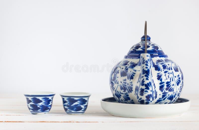 Taza de té miniatura con el pote del té en el tablero de madera blanco imagen de archivo