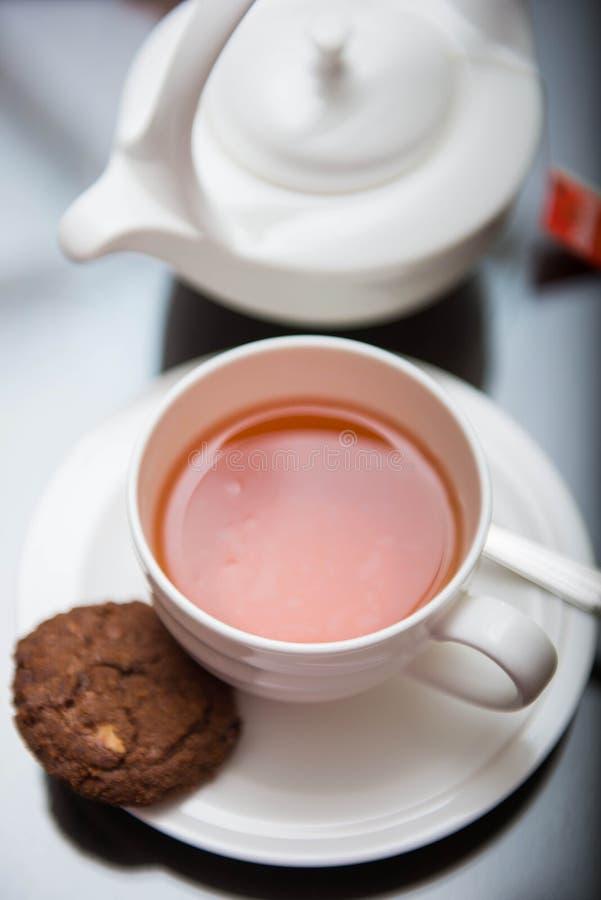 Taza de té negro con la galleta imagenes de archivo