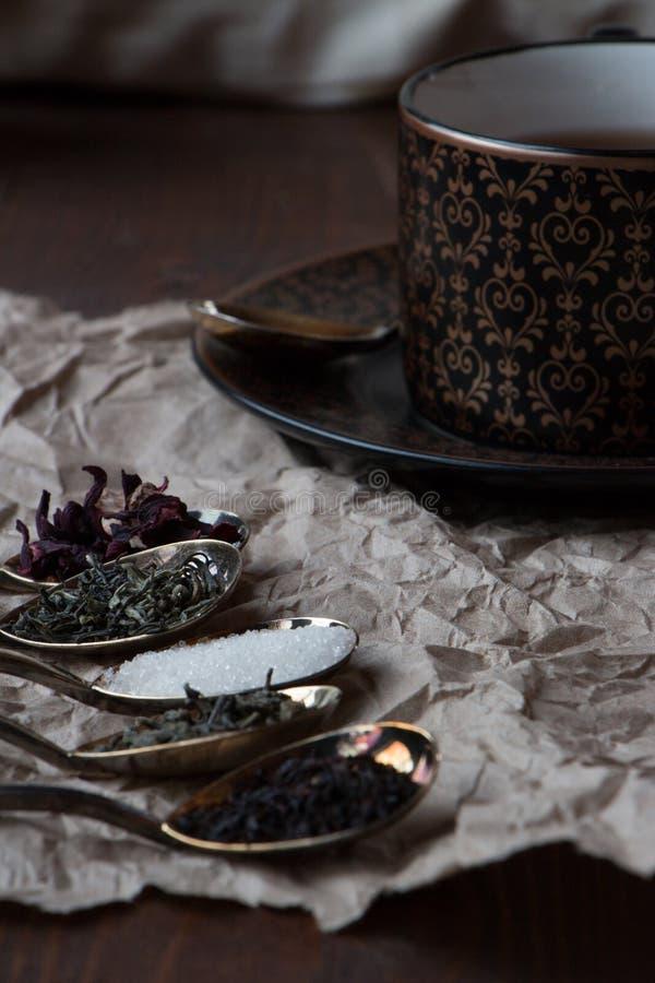 Taza de té negro con las cucharas de oro y verde, negro y té del carcade, fotos de archivo