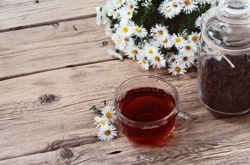 Taza de té negro con un ramo de margaritas imagen de archivo libre de regalías