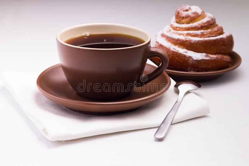 Taza de té negro en la servilleta blanca con el bollo dulce fotos de archivo