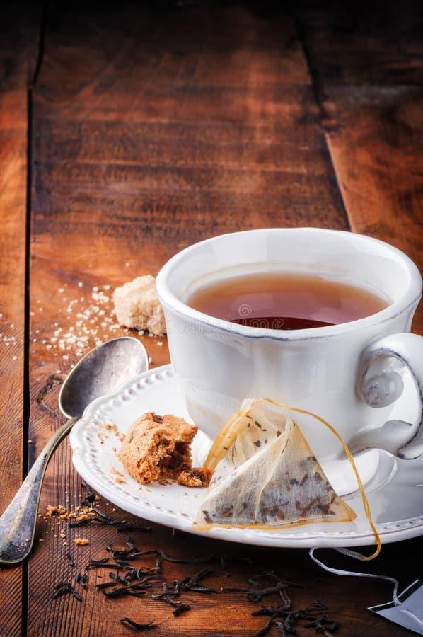 Taza de té negro y de galleta imagen de archivo libre de regalías