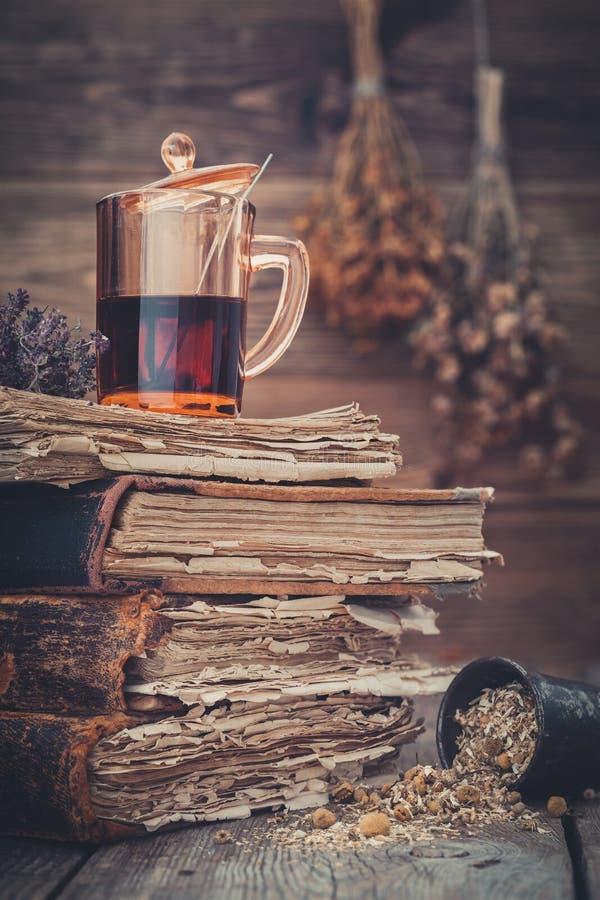 Taza de té sano o de tinte herbario en la pila de libros viejos, mortero de las hierbas de la margarita imagen de archivo