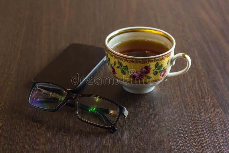Taza de té, teléfono móvil, lápiz, vidrios en la mesa de madera de la oficina foto de archivo libre de regalías