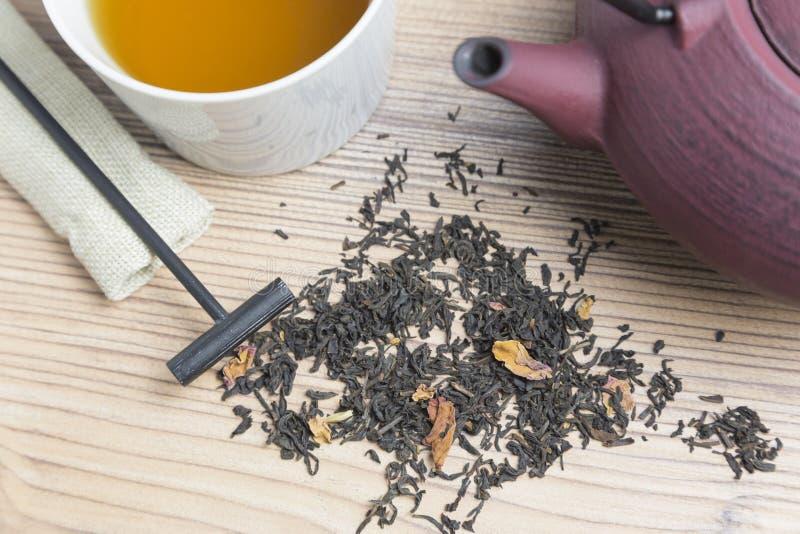 Taza de té, de tetera y de té negro en fondo de madera imagen de archivo libre de regalías