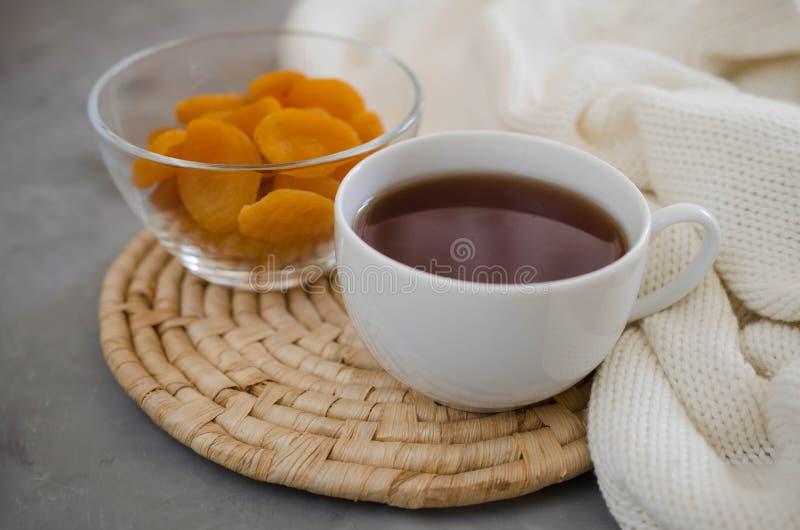 Taza de té y de albaricoques secados en una tabla, velas y una manta knited fotografía de archivo