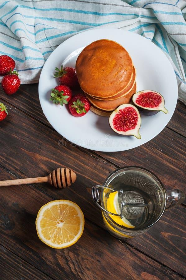 Taza de té y de crepes con los higos, fresas en el primer blanco de la placa fotografía de archivo