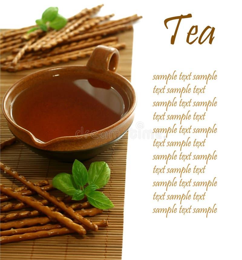 Taza de té y de palillos salados imagen de archivo libre de regalías