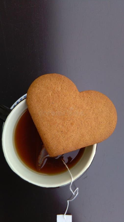 Taza de té y de galleta en forma de corazón imágenes de archivo libres de regalías