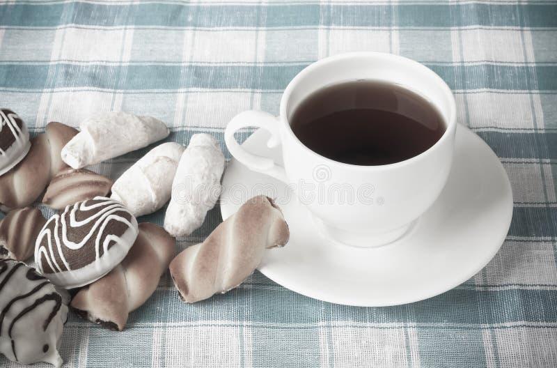 Taza de té y de galletas deliciosas en mantel a cuadros foto de archivo libre de regalías