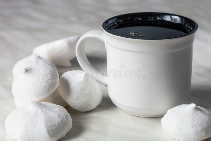 Taza de té y de merengues en la tabla imagenes de archivo