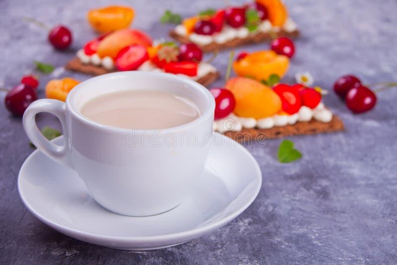 Taza de té y de pan quebradizo con queso, fruta y bayas de la nata fotografía de archivo