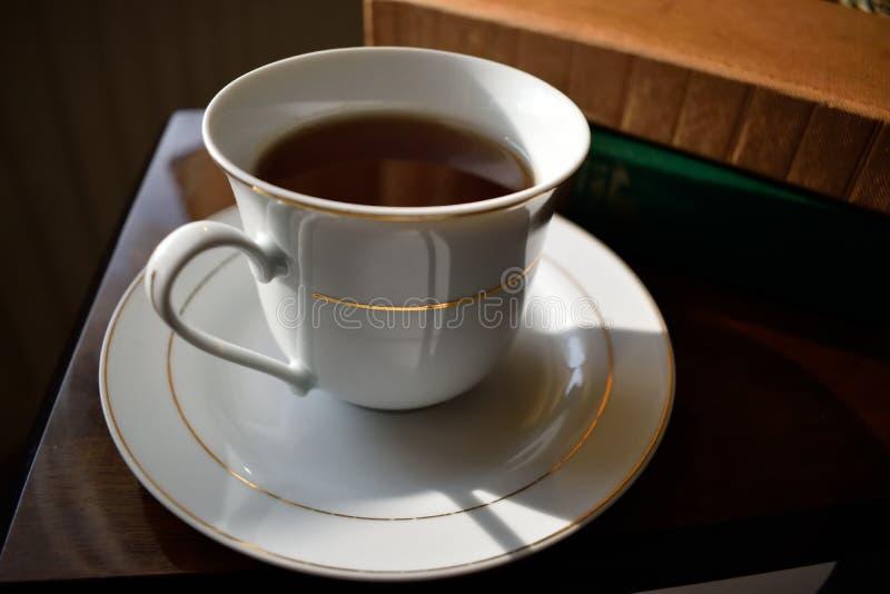 Taza de té y platillo blancos con los libros imagen de archivo libre de regalías