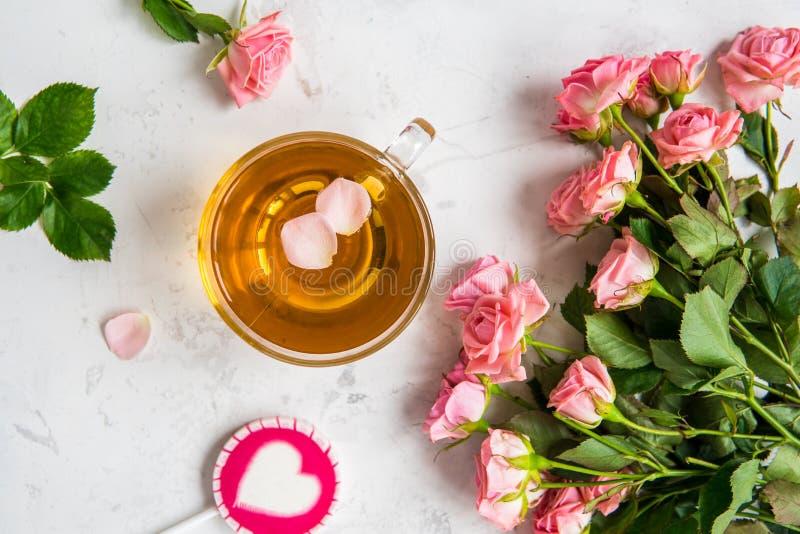 Taza de té y rosas rosadas blandas en un fondo blanco foto de archivo libre de regalías
